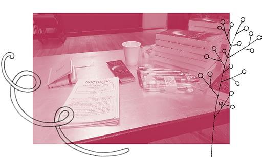 photographie d'une table de dédicaces traitée pour apparaître bicolore, avec quelques éléments graphiques abstraits